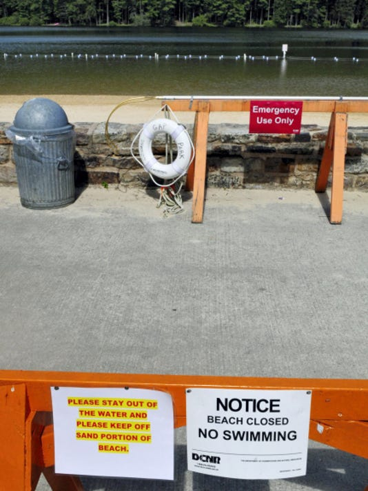 Markell DeLoatch — Public Opinion Signs warn visitors Thursday morning, July 23, 2015 that the beach is closed to swimmers at Cowans Gap Lake, near Fort Loudon, Pa. Suspected norovirus gastrointestinal illnesses led officials to close the lake to swimming, but officials have now decided it is safe to reopen the lake on Saturday.