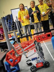 Wyatt Nelson, Aza Jafee and Luciano Hernandez of Mountain Mahogany Community School in Albuquerque guide their robot in competition during the VEX Robotics State Championship held February 2015 at New Mexico State University's Activity Center.