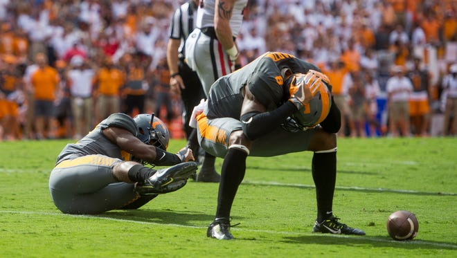 Vols defensive backs Justin Martin (8) and Micah Abernathy (22) react after dropping a possible interception during Tennessee's game against Georgia on Sept. 30.
