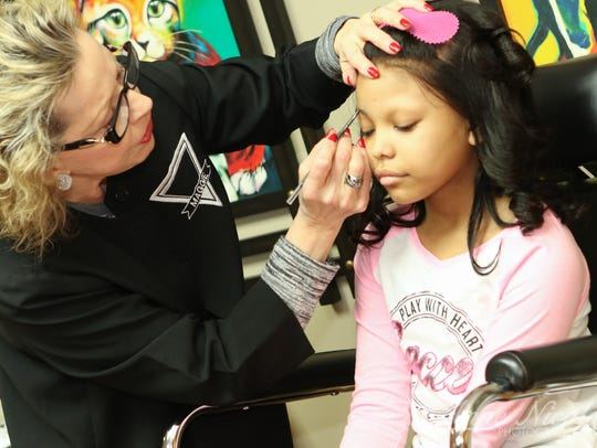 Wigs 4 Kids of Michigan CEO Maggie Varney works with