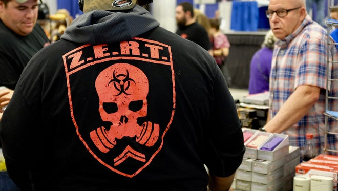 Leonard Lamar of the Louisiana Chapter of the Zombie Eradication Response Team talks to David Brackman, right, about the products at his Self Defense ATL booth.