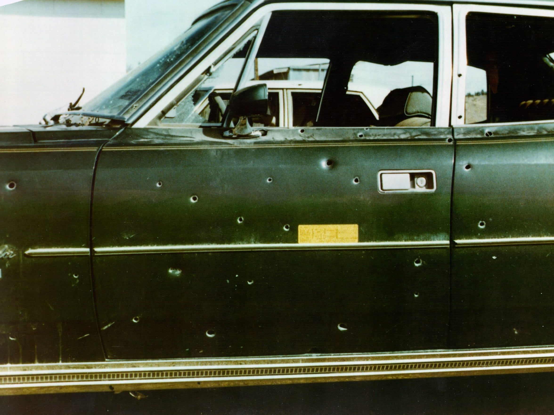 The car riddled with bullet holes.