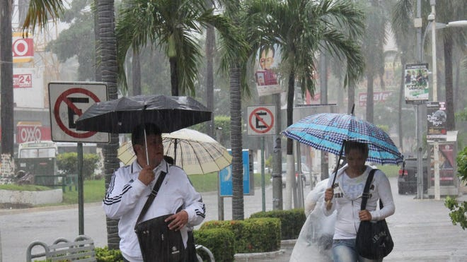 Heavy rains affect Mexico's Acapulco vacation resort during the passing of Hurricane Raymond on Monday.