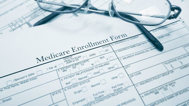 Eyeglasses sitting on Medicare enrollment form
