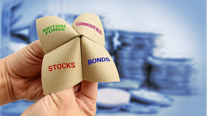 A child's folded paper finger toy is shown, with the words stocks, bonds, commodities, and mutual funds written on it.
