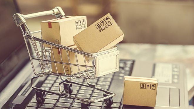 Miniature shopping cart with packages for shipping on top of a laptop.