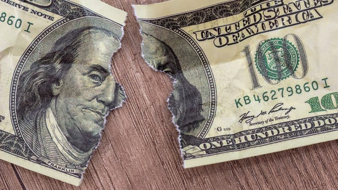 A ripped $100 bill on a wooden table