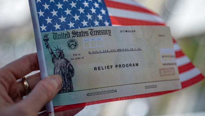 A relief check being held with an American flag.