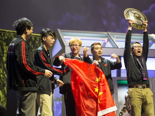 Members of Newbee esports Club hold the Aegis trophy, the top honor at The International Dota 2 Championship in Seattle in 2014.