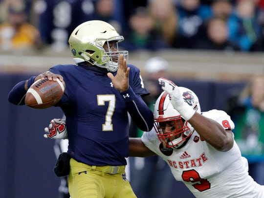 Notre Dame quarterback Brandon Wimbush (7) while being