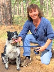 Jodie Canfield and her dog Nipsy, on lease, during a hike in the national forest.