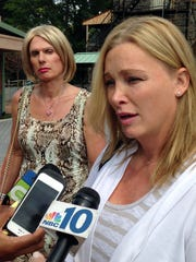 Christine Kitzler, left, a transgender woman from Myrtle Beach, S.C., looks on as her surgeon, Dr. Christine McGinn talks to reporters. speaks with reporters, Wednesday, Sept. 2, 2015, in Doylestown, Pa.  A judge has temporarily blocked Kitzler's gender-reassignment surgery for, while he considers her parents' request she be declared incompetent.