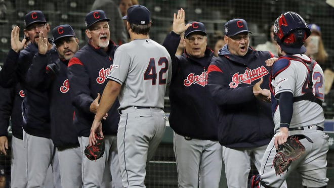 Indians manager Terry Francona, second from right, and other members of the coaching staff greet catcher Roberto Perez, right, and closing pitcher Brad Hand, center, after a game against the Seattle Mariners last season.