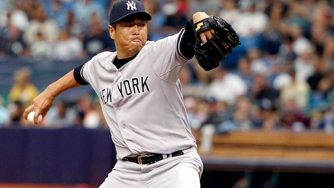 New York Yankees starting pitcher Hiroki Kuroda throws a pitch during the first inning against the Tampa Bay Rays at Tropicana Field. Kuroda pitched into the seventh inning for the Yankees.