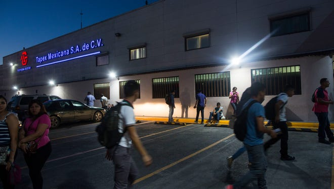 """In this March 21, 2017 photo, workers gather outside a """"maquiladora"""" for car accessories in Matamoros, Tamaulipas state, Mexico, across the border from Brownsville, Texas. Maquiladoras, as Mexican assembly plants are known, churn out everything from flat-screen televisions and washing machines to auto components that might cross borders a dozen times before a car comes off the assembly line in Michigan. (AP Photo/Rodrigo Abd)"""