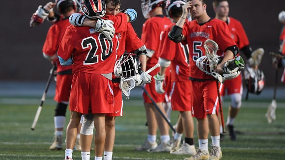 Greenville's Kian Razzaghy (20) hugs teammate Jacob Hall (22) after the Red Raiders' loss to Oceanside Collegiate Academy in the Class AAAA state final Saturday, April 28, 2018 at Irmo High in Columbia.