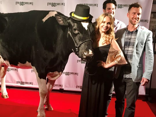 """The 60 Yard Line"" cast members Kim Crossman, from left, Nick Greco and Ryan Churchill pose with their co-star, Reaction the cow of Algoma, on the red carpet of the movie's world premiere Sunday night at the Wisconsin Film Festival in Madison."