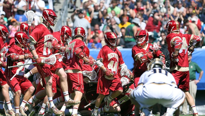 Denver Pioneers pile up on attacker Wesley Berg (14) after he scored the game winning goal against the Notre Dame Fighting Irish in overtime of the semifinals of the NCAA division I men's lacrosse championships at Lincoln Financial Field.