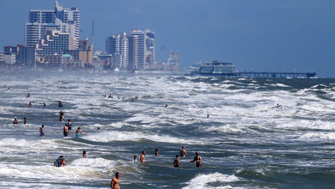 Beachgoers aren't deterred July 1, 2014, with the high surf and currents off Daytona Beach, Fla., that Tropical Storm Arthur is generating.