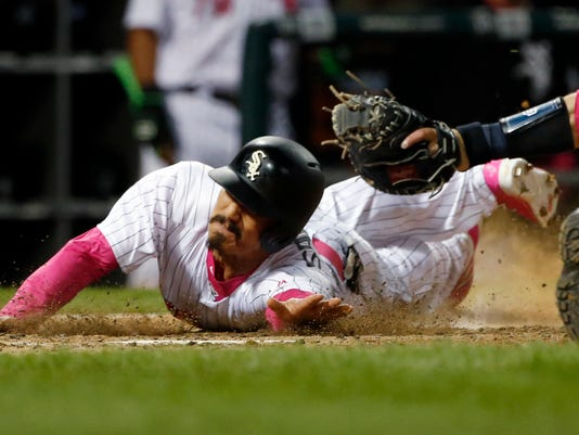 Chicago White Sox's Tyler Saladino, left, scores on a single by Yolmer Sanchez as San Diego Padres catcher Austin Hedges applies a late tag during the ninth inning of an interleague baseball game in Chicago, Saturday, May 13, 2017. (AP Photo/Nam Y. Huh)