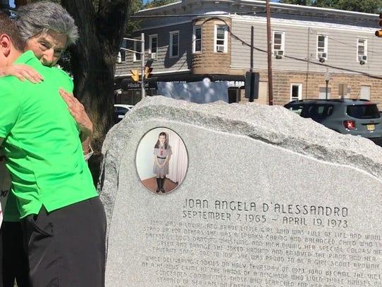 Rosemarie D'Alessandro hugs Michael Kazigian, 13, of