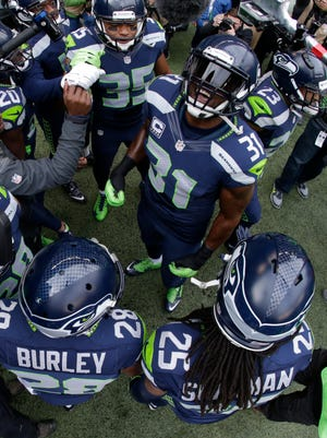 "The Seattle Seahawks ""Legion of Boom"" defensive players including Kam Chancellor (31) and Richard Sherman (25) huddle together outside the tunnel St. Louis Rams before taking the field for  in the first half of an NFL football game, Sunday, Dec. 28, 2014, in Seattle."