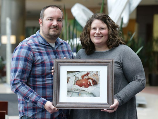 "Mark and Patricia Sweigart hold a photo of their daughter Josie whose death inspired them to create ""Josie's Impact,"" a pay it forward campaign in her honor, at Community North Hospital in Indianapolis on Monday, March 12, 2018. Josie lived 18 days after being born at 28 weeks."