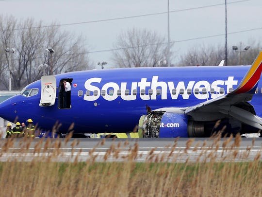 FILE- In this April 17, 2018, file photo a Southwest Airlines plane sits on the runway at the Philadelphia International Airport after it made an emergency landing in Philadelphia. In new accounts released Wednesday, Nov. 14, into the April accident, the flight attendants described being unable to bring the woman back in the plane until two male passengers stepped in to help. The flight attendants told investigators at least one of the men put his arm out of the window and wrapped it around the woman's shoulder to help pull her back in. (David Maialetti/The Philadelphia Inquirer via AP)