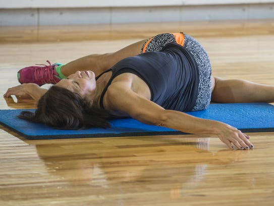 Instructor Rhea Hibbert demonstrates stretching on