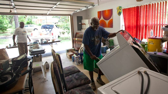 Buster Leon, left, purchased a washing mashing at Rudy Slaughter's garage sale in Tallahassee, Fla.