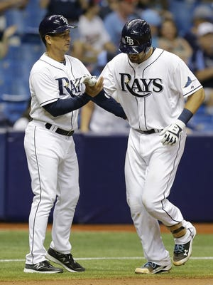 Tampa Bay Rays catcher Curt Casali, right, is held up briefly by third base coach Charlie Montoyo after injuring himself running around the bases after hitting a home run against the Minnesota Twins on Tuesday, Aug. 25, 2015, in St. Petersburg, Fla.