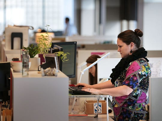 Interior Designer Melanie Newport works at her standing desk in the new offices of HBG Design on the 23rd floor of One Commerce Square which have a clean and open layout that takes full advantage of Memphis view.