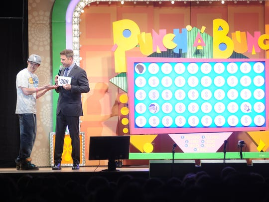 """""""The Price Is Right Live"""" host Mark L. Walberg, right, shows contestant Christopher Demetriow, left, of Poughkeepsie, his prize in the Punch-a-Bunch game in the Mid-Hudson Civic Center in this file photo from 2015."""