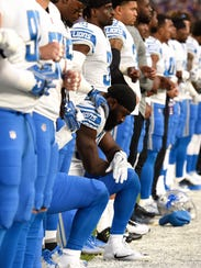 The Lions' Steve Longa (54) takes a knee with teammate