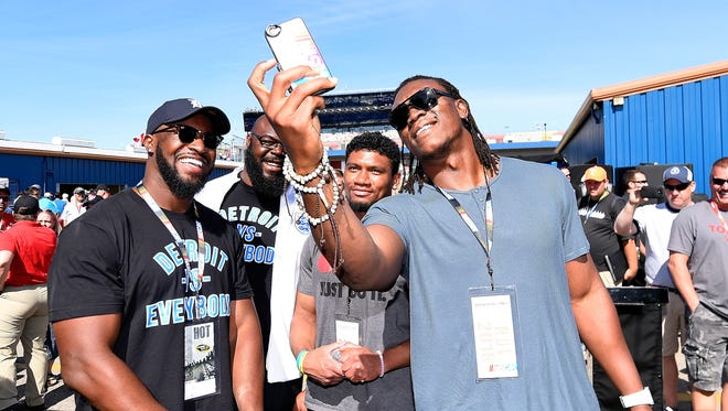 From left, linebacker Antwione Williams, defensive tackle A'Shawn Robinson, cornerback Ian Wells and defensive end Ziggy Ansah of the Detroit Lions tour the garage area before Sunday's race.