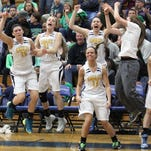 The Hartland bench erupts in celebration as team mates on the court bring the Eagles within striking distance to tie Heritage late in the fourth quarter at Carman Ainsworth.