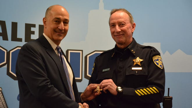 Salem Police Departments new Deputy Police Chief George Burke, left, shakes the hand of Chief Jerry Moore at his swearing in ceremony at the Salem Library on Tuesday, Jan. 3.