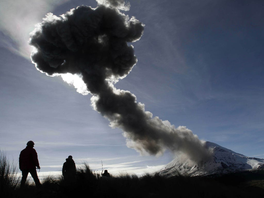 People watch the Popocatepetl volcano erupt on Dec. 28 at Paso de Cortes in Puebla State, Mexico.