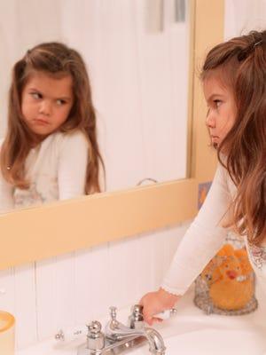 Young girl (6-7), looking in bathroom mirror,