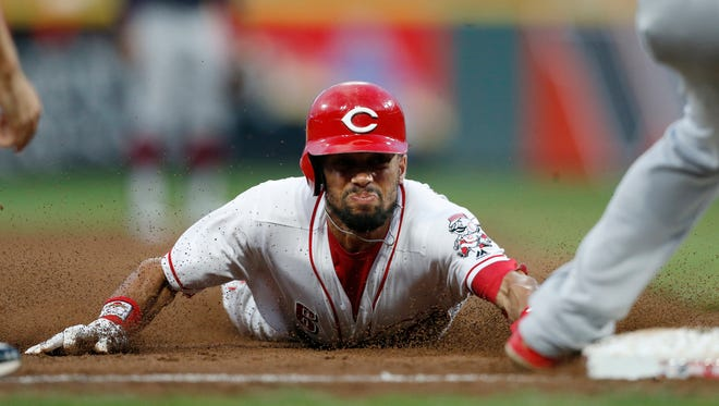 Cincinnati Reds' Billy Hamilton slides safely into third base as he advances on a wild pitch by Cleveland Indians starter Shane Bieber during the second inning of a baseball game Wednesday, Aug. 15, 2018, in Cincinnati. At right is third baseman Jose Ramirez.