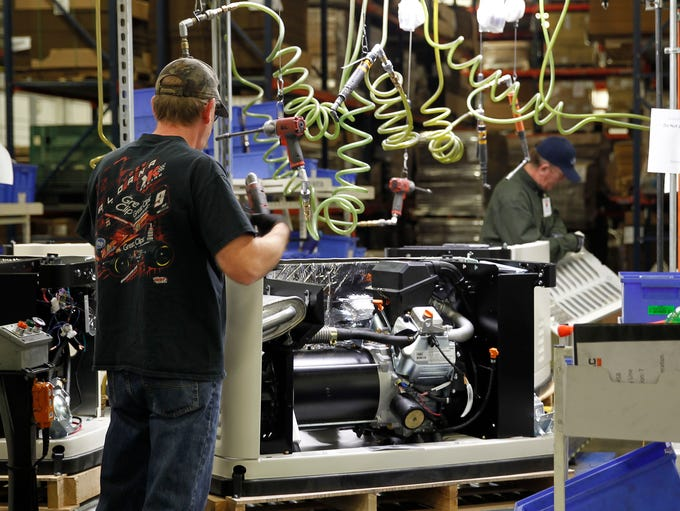 Workers assemble parts at Generac in the home standby