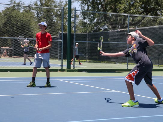 Cole Taylor and Zachary Carpenter play tennis during