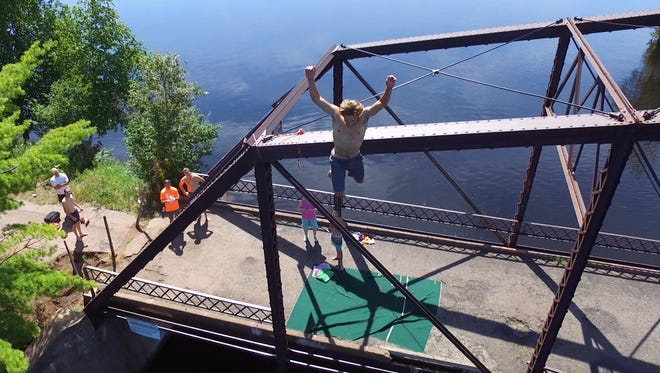Owen Gibson jumps off a bridge in Michigan's Upper Peninsula as part of a quest to check items off a bucket list with friends Gregory Smith, Nick Smith and Kevin Reardon.