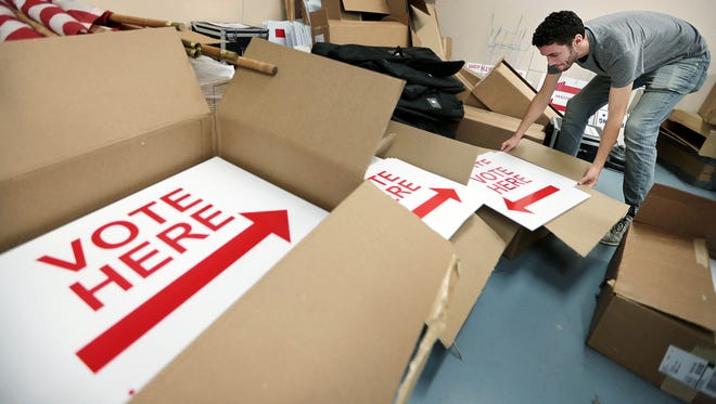 Election Commission official Parker Mulherin rearranges boxes of voting signs at the Shelby County Election Commission.