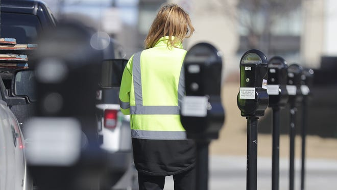 A City of Green Bay parking enforcement officer checks parking meters along Washington Street on Monday in Green Bay.