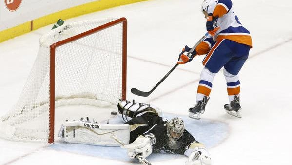New York Islanders right wing Kyle Okposo (top) scores the game-winning goal past Pittsburgh Penguins goalie Marc-Andre Fleury (29) during the shootout at the CONSOL Energy Center. The Islanders won 5-4 in a shootout.