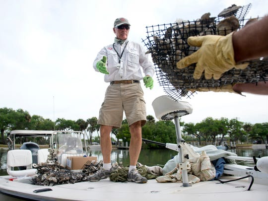Paul Dritenbas loads oyster mats onto his boat while volunteering with the Vero Beach Power Squadron on March 29, 2014.