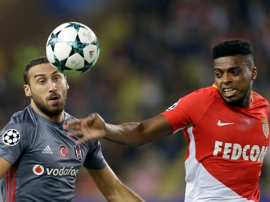 Besiktas' Cenk Tosun, left, challenges for the ball with Monaco's Jemerson during the Champions League Group G first leg soccer match between Monaco and Besiktas at Louis II stadium in Monaco, Tuesday, Oct. 17, 2017. (AP Photo/Claude Paris)