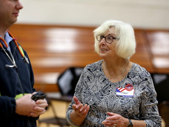 June LaPille, poll worker talks with a voter Tuesday November 3, 2015 at the Springdale Community Center. LaPille, 79, of Springdale a native of London, England, said it was her civic duty to volunteer after she became a U.S. citizen, she has been working the polls for about 20 years.