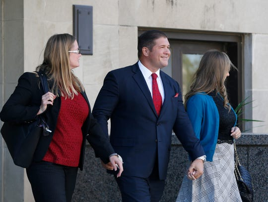 Jesse Benton (center) smiles as he leaves from his